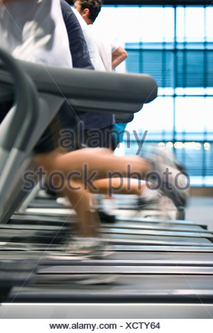 People running on treadmills in health club - Stock Photo