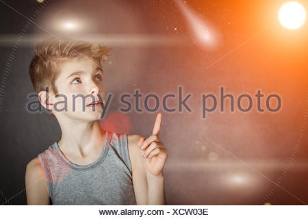 Curious Boy Pointing his Up to Glowing Lights - Stock Photo