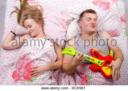 Young couple lying in bed. Husband plays guitar and shouts of his voice. Wife next sleeps. - Stock Photo