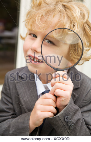 Boy using magnifying glass outdoors - Stock Photo