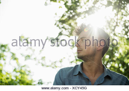 Portrait of serious young man in park - Stock Photo