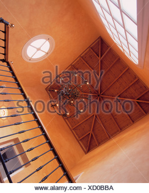 Looking up at wooden ceiling and metal chandelier in terracotta Spanish hall - Stock Photo