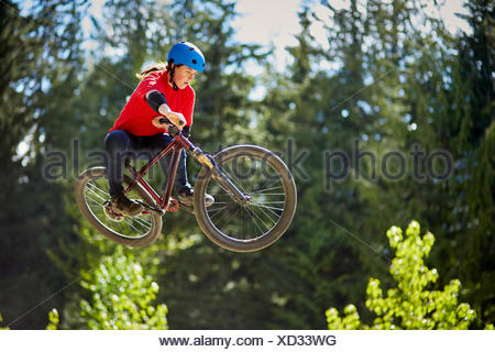 Young female bmx biker jumping mid air in forest - Stock Photo