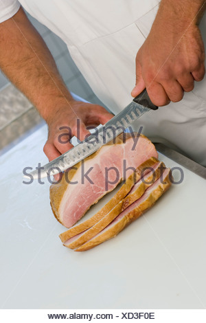 Butcher slicing meat - Stock Photo