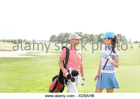 Male and female golfers communicating at golf course - Stock Photo