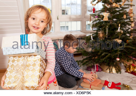 Little girl holding gift boxes, brother in background, Munich, Bavaria, Germany - Stock Photo