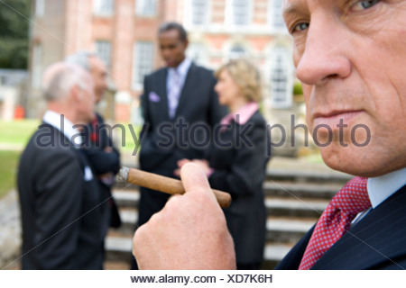 Businessman with cigar by manor house, colleagues in background, close-up - Stock Photo