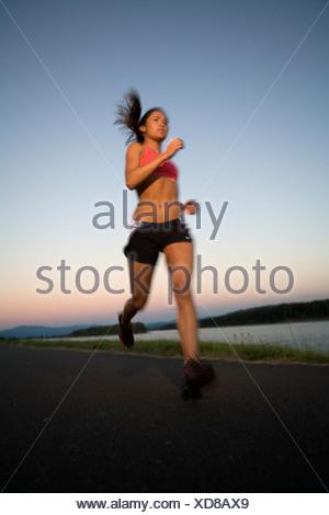 Asian American (Vietnamese) woman runs along road or riverside trail at sunset, Columbia River, Portland, Oregon - Stock Photo