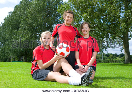 Portrait of smiling teenage girls in soccer uniforms - Stock Photo