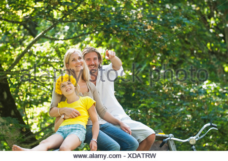 Austria, Salzburg County, Family sitting on fence - Stock Photo