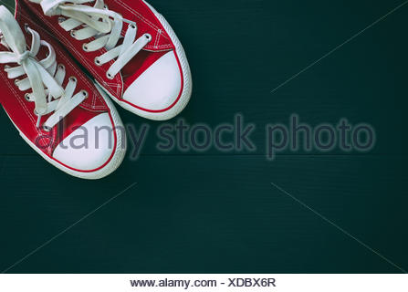 pair of red sneakers youth on a black wooden background, empty space - Stock Photo