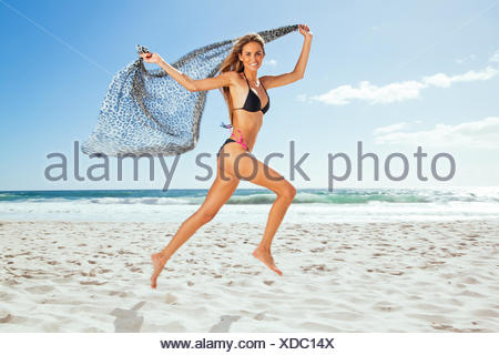 Young woman running along beach holding a scarf - Stock Photo