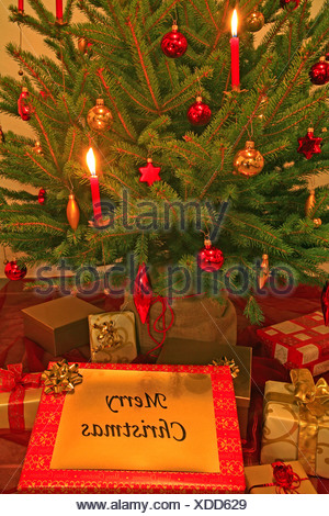 Decorated christmas tree with candles and porcelain ornaments, presents under the tree - Stock Photo