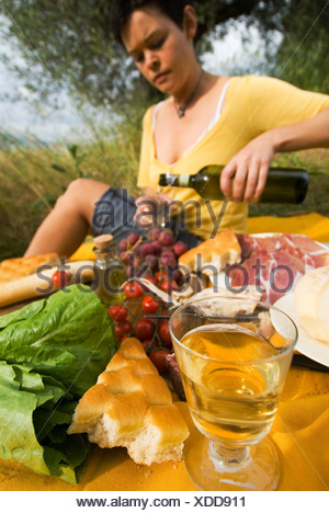Woman Pouring Bottle Of Wine In Preparation For Picnic Under Olive Trees - Stock Photo