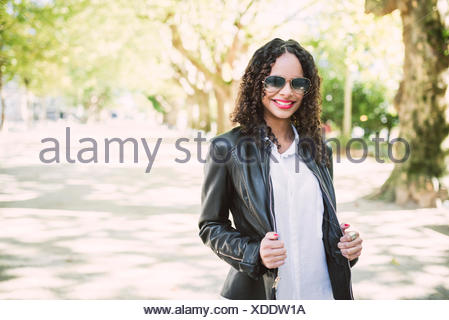 Portrait of smiling woman wearing sunglasses and leather jacket in a park - Stock Photo