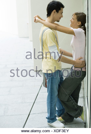 Teenage couple standing with arms around each other, leaning against wall - Stock Photo