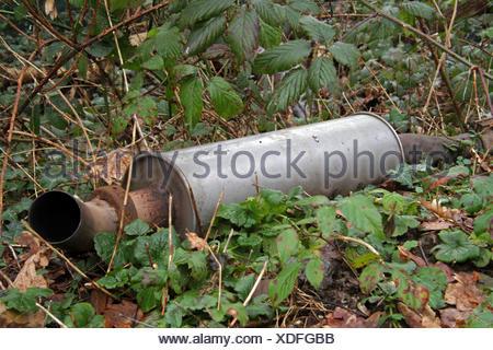 alte am Waldrand illegal entsorgte Auspuffanlage , Deutschland | illegal disposed exhaust system at the edge of a forest, German - Stock Photo