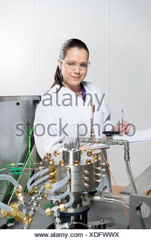 Portrait of female scientist, doing research on a innovative technology for mixing chemicals, at a hightech startup company - Stock Photo