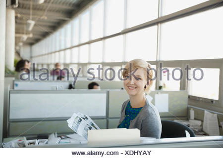 Confident businesswoman smiling in office - Stock Photo
