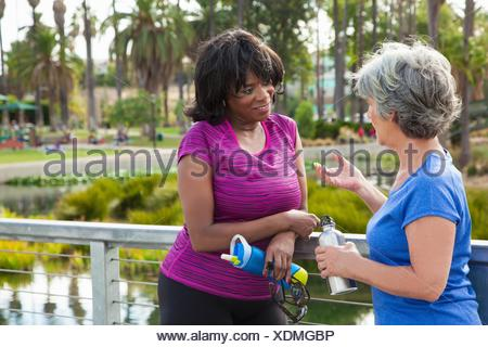 Mature female friends in park, talking, holding water bottles - Stock Photo