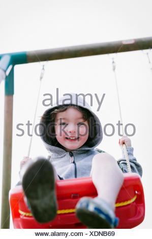 A boy in a hooded fleece, sitting on a swing - Stock Photo