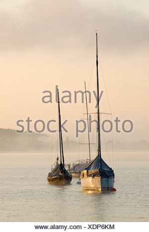 The first light of the day hits sailing boats in front of thick morning fog at Ammersee lake near Schondorf, Bavaria, Germany,  - Stock Photo