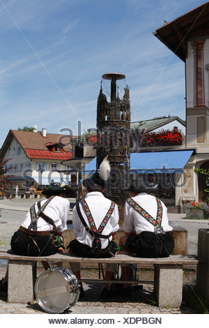 Three young men wearing traditional Lederhosen in front of the fountain on Dorfstrasse, Oberammergau, Upper Bavaria, Germany, E - Stock Photo