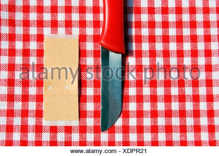 Red knife and band-aid on plaid tablecloth - Stock Photo