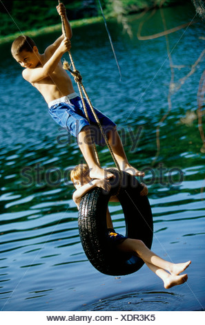 Two boys playing on a tire swing - Stock Photo