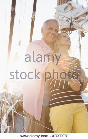 senior couple hugging on sailboat - Stock Photo