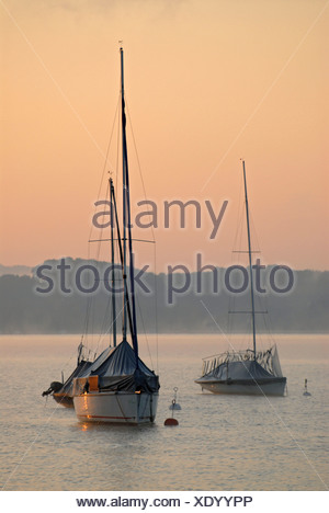 The first light of the day hits sailing boats at Ammersee near Schondorf, Bavaria, Germany, Europe - Stock Photo