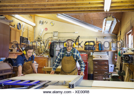 Carpenters using table saw in workshop - Stock Photo