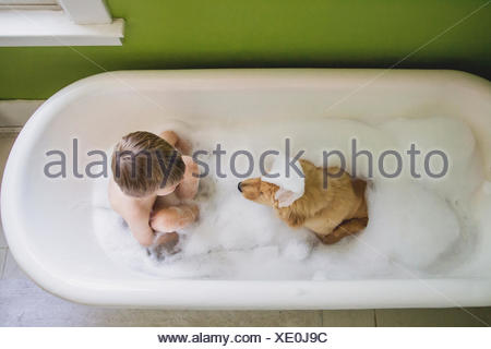 Boy and dog sitting in bathtub - Stock Photo