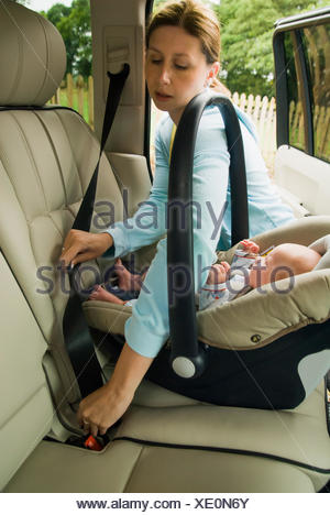 Mother strapping baby son in back seat of a car - Stock Photo