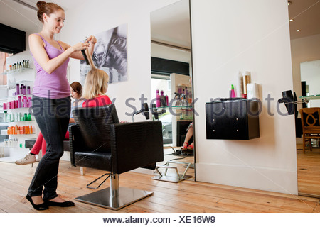 A female hairdresser cutting a young girls hair in a hairdressing salon - Stock Photo