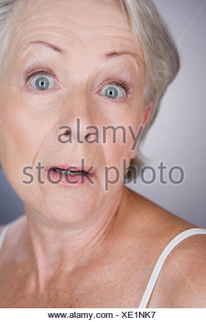A senior woman looking shocked - Stock Photo