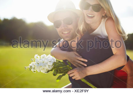 Young woman with flowers getting piggy back from boyfriend in park - Stock Photo
