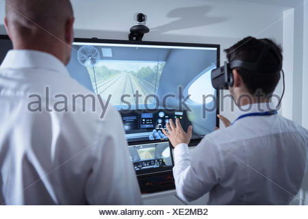 Instructor and apprentice using Virtual Reality system in railway engineering facility - Stock Photo