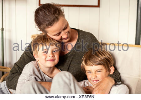 Sweden, Uppland, Runmaro, Barrskar, Portrait of mother with two sons (4-5, 6-7) - Stock Photo
