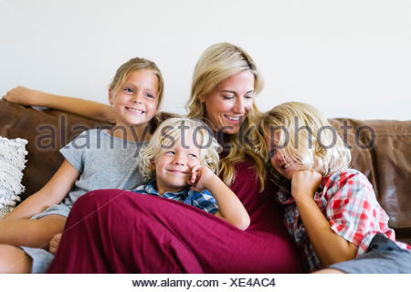 Mother and children (4-5, 6-7, 8-9) resting in living room - Stock Photo