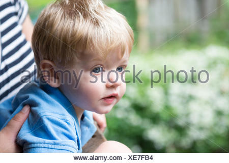 Boy sitting on mother's lap - Stock Photo