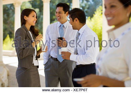 Small group of business colleagues standing in colonnade holding paper cups talking side view - Stock Photo