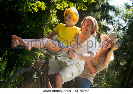 Austria, Salzburg County, Family sitting on old bicycle - Stock Photo