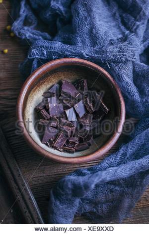 Dark chocolate chunks in a small bowl - Stock Photo