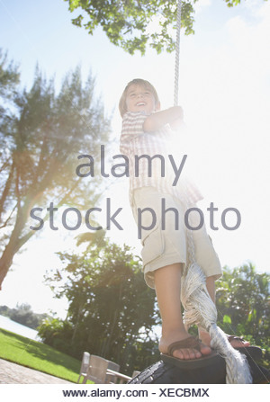 Young boy outdoors at park playing on tire swing - Stock Photo