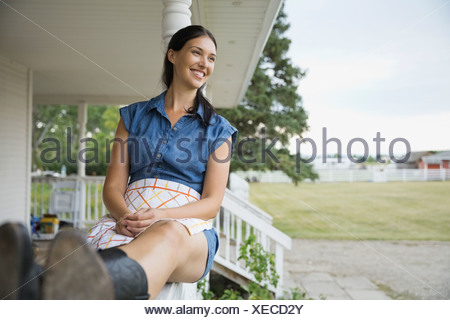 Smiling woman sitting on porch railing - Stock Photo