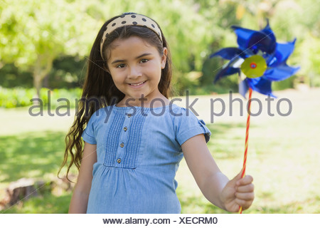 Cute little girl holding pinwheel at park - Stock Photo