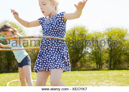 Low angle view of two girls playing with plastic hoops - Stock Photo