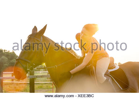 Woman on horseback petting horse in rural pasture - Stock Photo