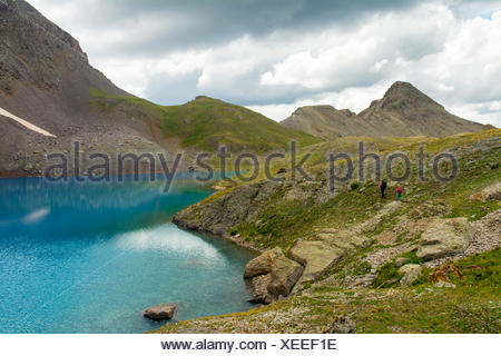 A woman and her daughter hiking past a blue lake, San Juan National Forest,  Silverton, Colorado. - Stock Photo